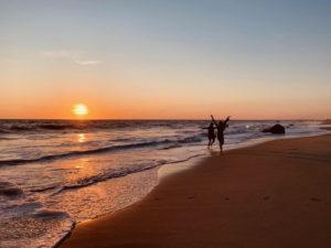 Janine & Lisa running playfully down the beach at sunset in Martha's Vineyard, Sept. 2019