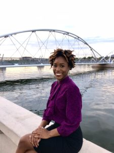 Olivia Watkins seated at the side of Tempe Town Lake, with the pedestrian bridge in the background.